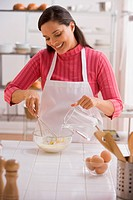 Hispanic woman mixing batter