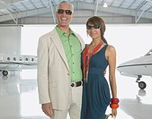 Couple hugging in airplane hanger, Nobato, California, United States