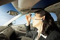 Businesswoman driving and putting on makeup, San Rafael, California, United States