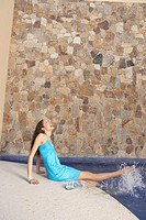 Woman kicking her feet in hotel pool, Los Cabos, Mexico