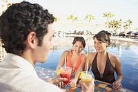 Two Hispanic women getting drinks at a hotel pool bar, Los Cabos, Mexico