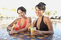 Two Hispanic women at hotel pool bar, Los Cabos, Mexico