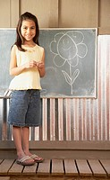 Hispanic girl drawing on blackboard