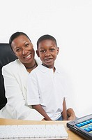 African businesswoman sitting at her desk with her young son, San Rafael, California, United States