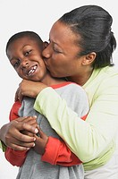 Studio shot of African mother hugging and kissing her young son, San Rafael, California, United States