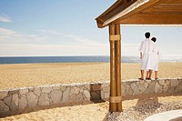 Couple in bathrobes at beach, Los Cabos, Mexico