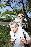 Hispanic grandfather holding grandson on his shoulders outdoors