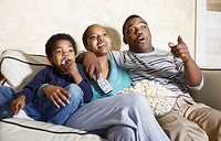 African American family watching television with popcorn