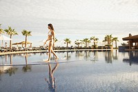 Woman walking in resort hotel pool, Los Cabos, Mexico