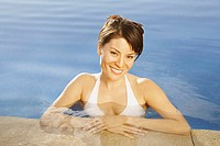 Hispanic woman smiling in hotel pool, Los Cabos, Mexico