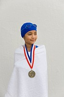 Hispanic girl wrapped in towel with swimming metal