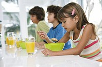 Three kids (8-10) at table, having breakfast