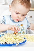 Baby boy (9-12 months) playing with pasta in high chair, close-up