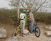 Young couple with mountain bikes, looking at map