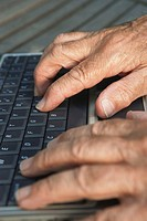Senior man using laptop, close-up