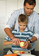 Father assisting son (10-12) peel apple