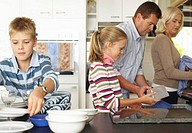 Family tidying kitchen (focus on girl (10-12) putting containers away)