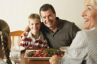 Family at dinner table, portrait of father with arm around son (10-12), smiling
