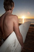 Teenage boy (15-17) on beach holding surfboard, dawn, rear view