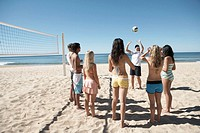 Young woman demonstrating volley ball to teenagers on beach