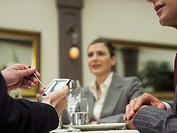Businesspeople in restaurant, man using electronic organiser, close-up