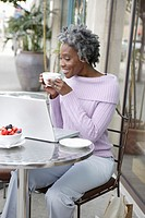 Senior woman using laptop computer at outdoor restaurant, side view