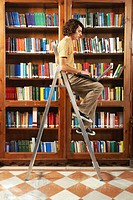 Young man sitting on step ladder in library using laptop, side view