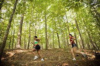 Two women running in woods