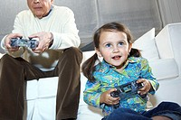 Grandfather and granddaugther (2-4) playing video game, ground view,