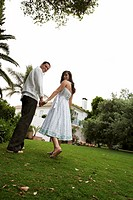 Couple holding hands, looking over shoulders, portrait, low angle view