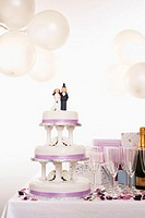 Wedding cake decorated with bride and groom figures on table