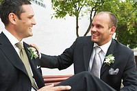 Groom and best man smiling at each other