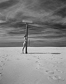Nude woman standing behind pole on beach, b&w