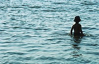Child standing waist deep in water