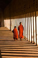 Young monks walk through a hallway in the Shwezigon Pagoda as light streams in through the pillars, Bagan, Myanmar (Burma)