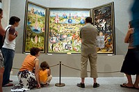 A group of people admire Hieronymus Bosch's 16th century painting 'The Garden of Earthly Delights' inside the Museo del Prado, Madrid, Spain