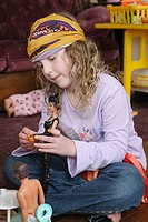 Girl, age 8 or 9, wearing Survivor buff on head, sitting on floor playing with Barbies, toys and couch in background