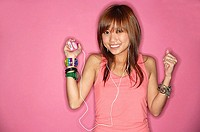 Young woman smiling, listening to mp3 player
