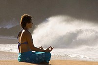 Young woman meditating on beach, next to waves