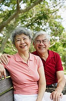 Mature couple on park bench, looking at camera