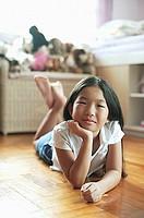 Girl in bedroom, lying on floor, hand on chin