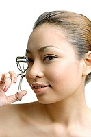 Young woman using eyelash curler, looking at camera
