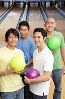 Men in bowling alley, holding bowling balls, looking at camera