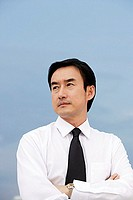 Businessman with arms crossed, looking away