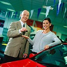 portrait of a car salesman handing over a set of keys to a young woman (tungsten)