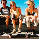 portrait of a man and two young women sitting on a wall with a skateboard