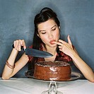 a young woman sitting in front of a chocolate cake with a knife and licking her fingers