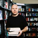 portrait of a man holding a pile of books in a library