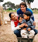 a father pushing his wife and children in a wheelbarrow