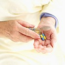 elderly woman taking medicine pills from container